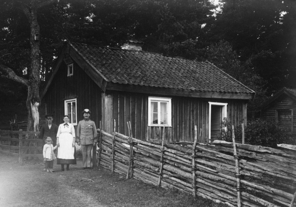 Family of four in front of a croft.