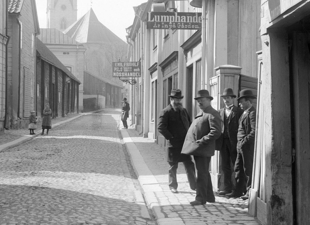 A cobbled street with four men under a sign.