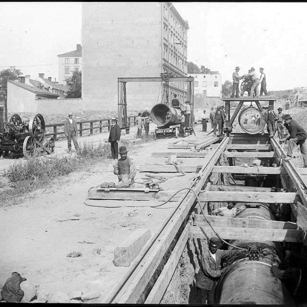 Twenty men laying pipes and a few buildings.