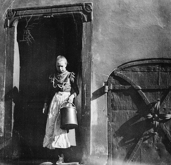 A young woman with a bucket come out a door.