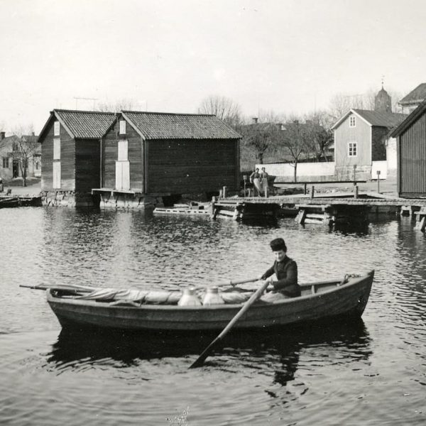 A woman rowing in a harbor.
