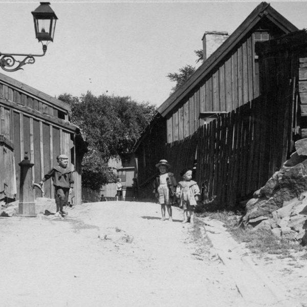 Three children on a cobble street