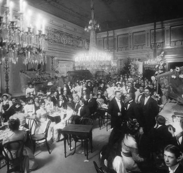 A party hall with people in ballgowns and tailcoats.