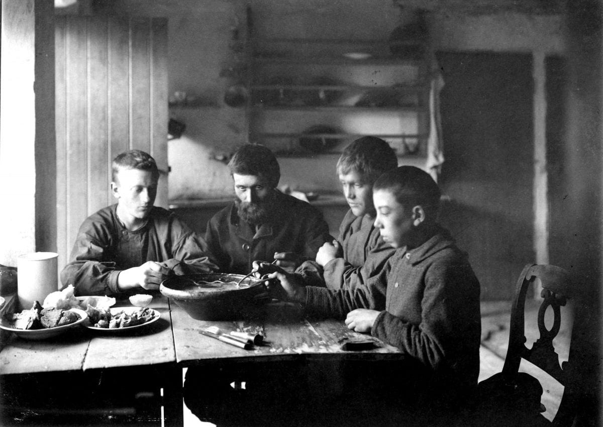 Three boys and a man at a dinner table.