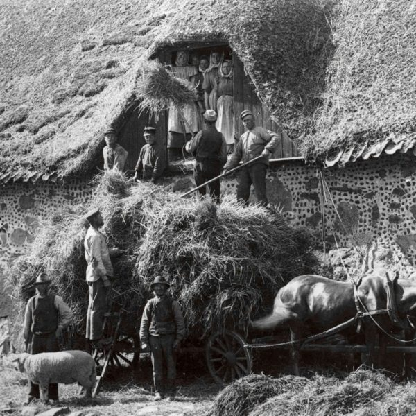 A haycart at a stone barn and 12 workers.