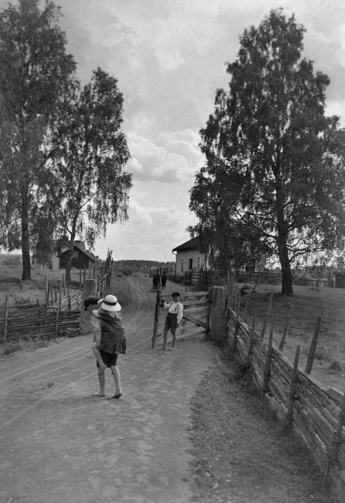 Children at a gate on a dirt road