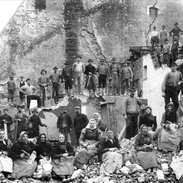 A large team of workers at a demolished building.