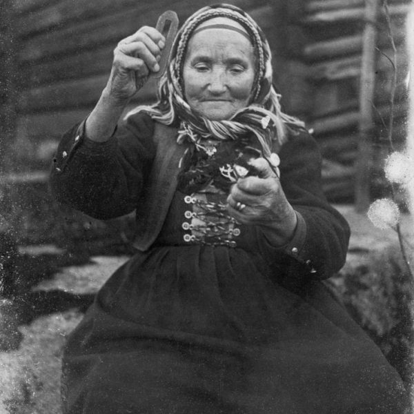 A very old woman making fire