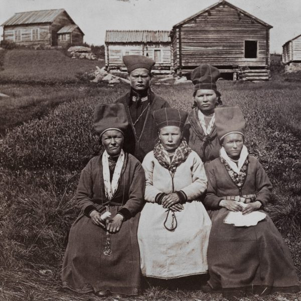 Group photo of four women and a man in front of lodges.