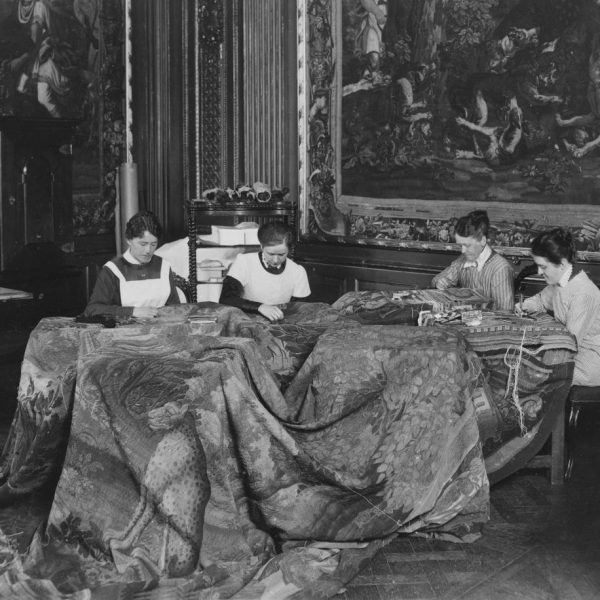 Four women at a table, working on a large tapestry.