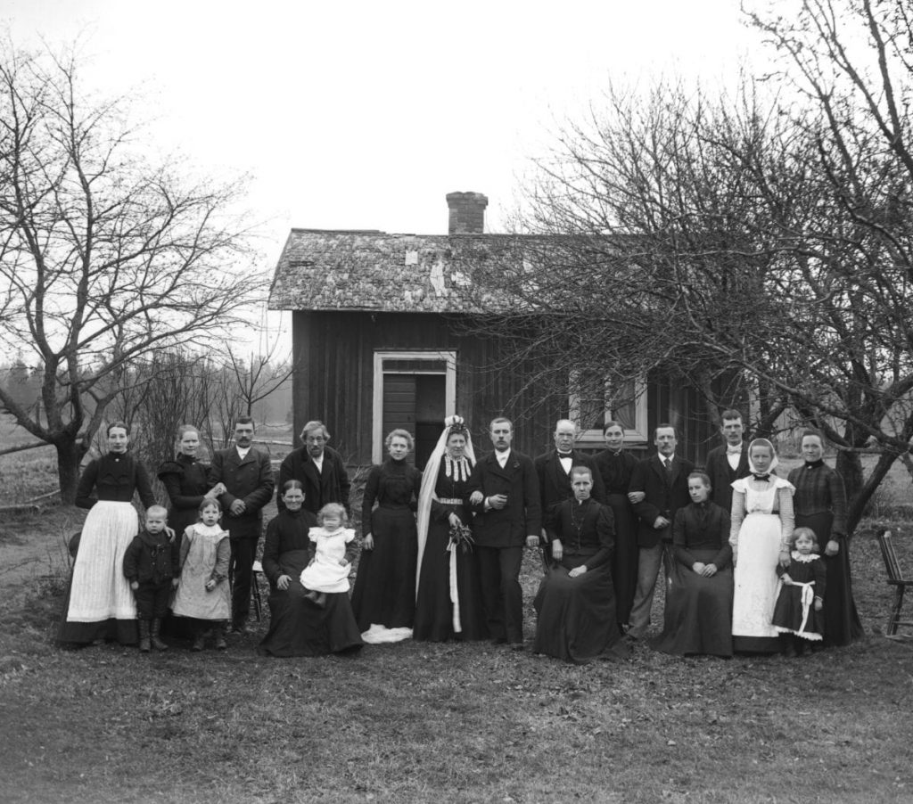 A bridal couple and eighteen others in front of a cottage.