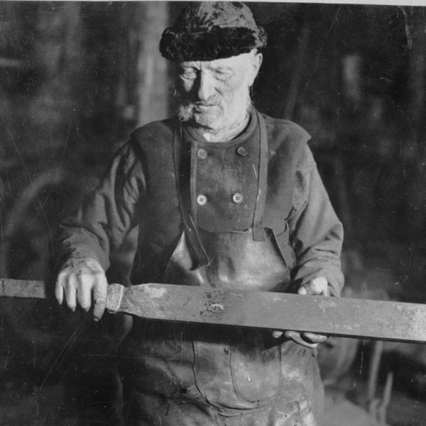 A smith holding a piece of iron.