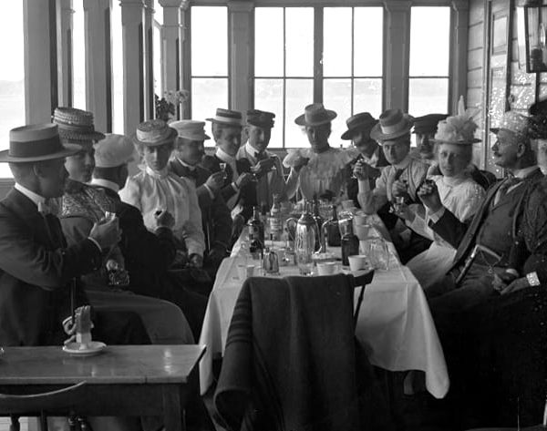 Fourteen people at a table raising their glasses