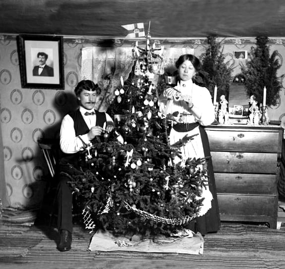 A man and a woman at a Christmas tree