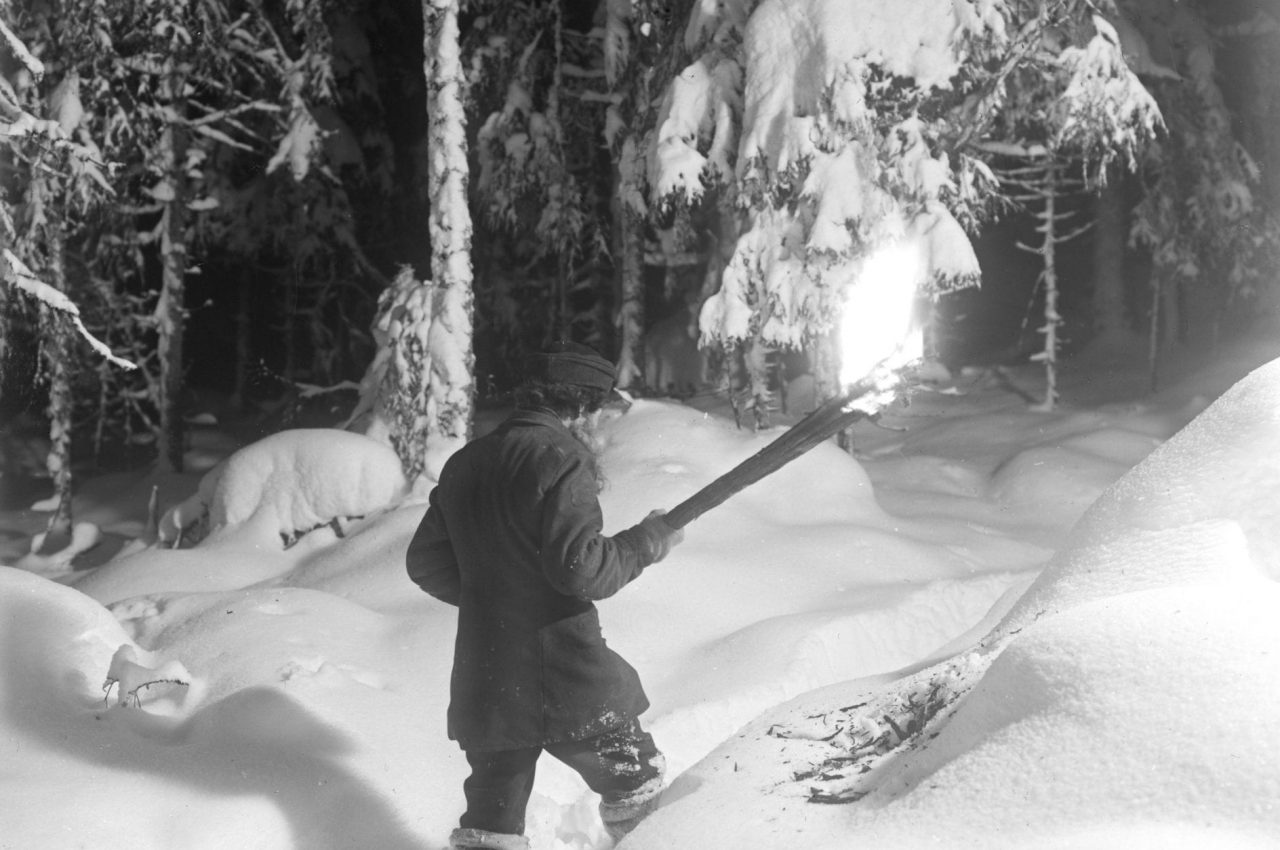 A man holding a torch walking in deep snow.