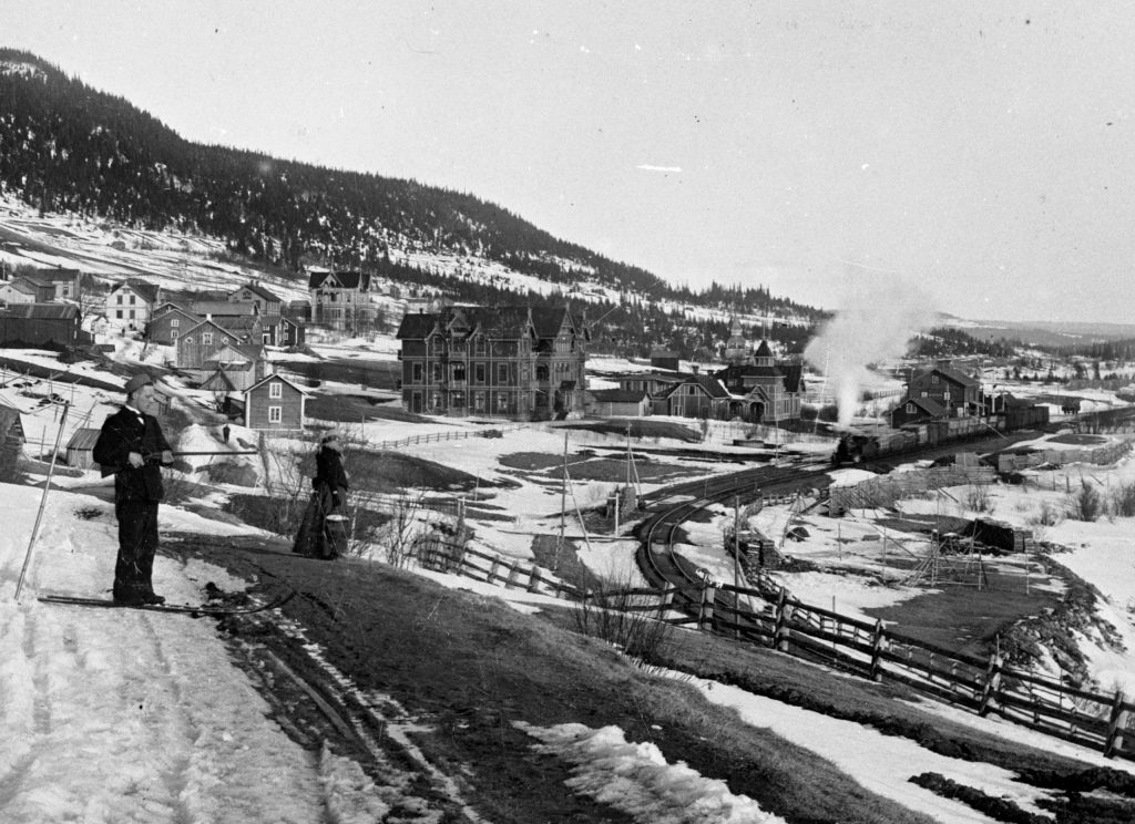 Hills with snow, houses, and a steam railway. A woman in black and a man on skis with a gun.