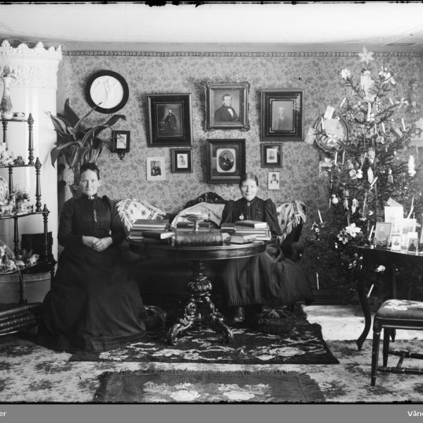 Two older women on a couch with a Christmas tree to the right and a mansonry heater to the left and tons of Victorian style decorations.